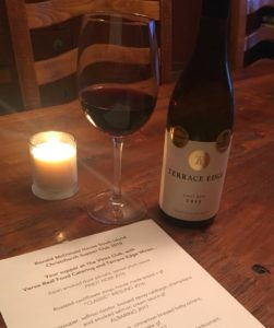 Glass of red wine on wooden table next to candle and bottle of wine. Also a menu showing just a teaser of what's to eat.