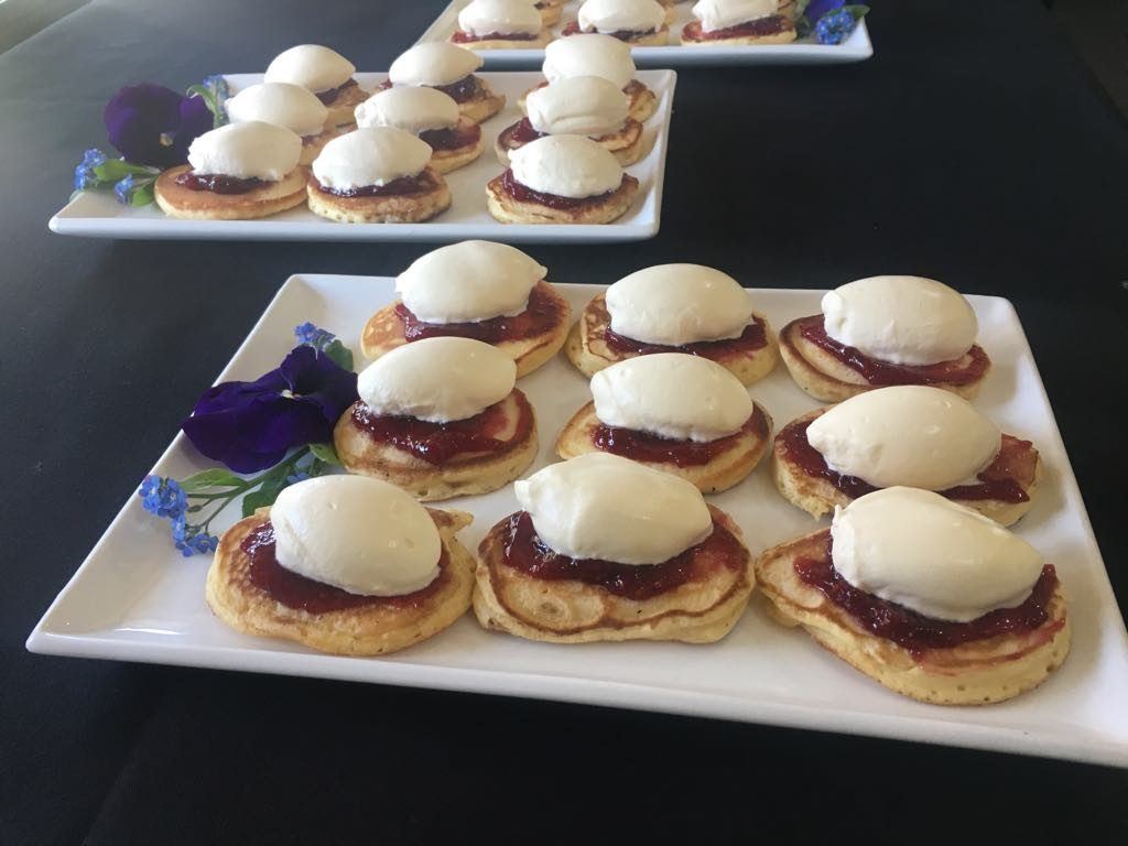 Two plates of nine pikelets with jam and cream on top, and some spring flowers decorating the square plates they're served on
