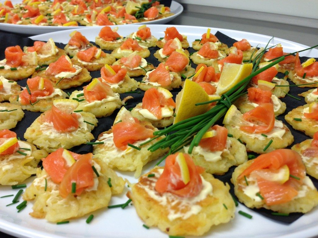 Oval platter with small salmon blini canapes garnished with lemon